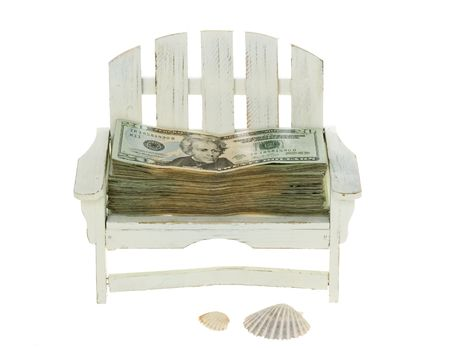 Big Stack of US Currency Twenty Dollar Bills lying in a miniature white adirondack chair with beach shells,  isolated on white background. photo