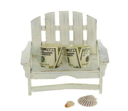 Two Fifty Dollar Bills Seated in a miniature white adirondack chair,  isolated on white background with two beach shells. photo