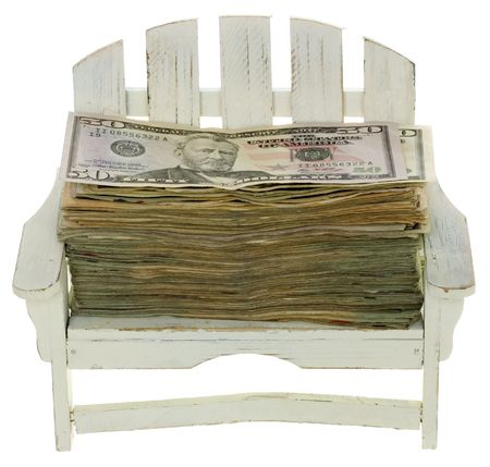 Big Stack of US Currency Twenty Dollar Bills lying in a miniature white adirondack chair,  isolated on white background. photo