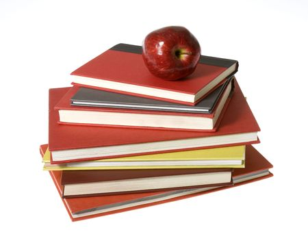 top seven: Shiny, bright red apple on its side sitting on top of a pile of colorful red, maroon,lime green, gray , and orange books stacked. Seven books in total. isolated on white.
