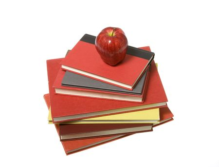 top seven: Shiny, bright red apple sitting on top of a pile of colorful red, maroon,lime green, grey, and orange books stacked. Photo taken aerial point of view. Seven books in total. isolated on white. 5750