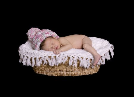 Newborn with snow hat sleeping on baby blanket in basket. isolated over black. photo