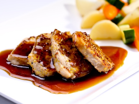 Pork fillet with seasonal vegetables and balsamic reduction Stock Photo