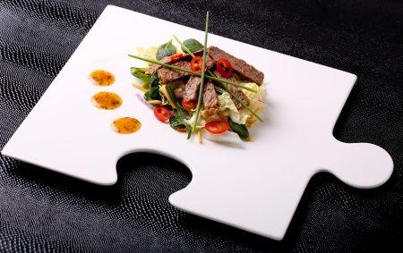 Thai Beef Salad on Modern Puzzle Plate Stock Photo