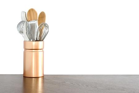 Kitchen utensils in ceramic container on white