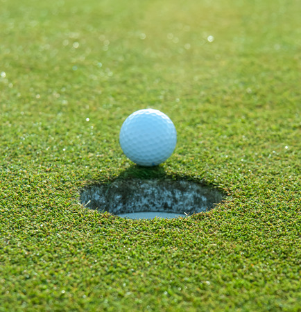A white golf ball rests just before falling into the hole