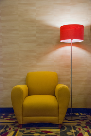 lamp shade: A yellow chair and lamp against the wall