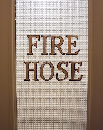 Painted words mark that a closet holds a fire hose
