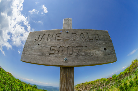 appalachian trail sign: A fisheye lense captures the brilliant blue sky above the Jane Bald elevation marker Stock Photo