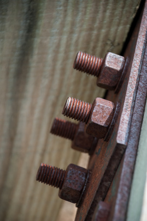 Rusty bolts hold up a large wooden railing