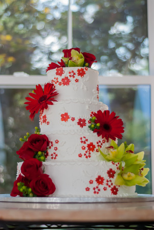 A buttercream frosted cake is decorated with frosted and real flowers