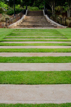 stepping: Concrete stepping stones mark the walkway to a set of stairs across a green lawn Stock Photo