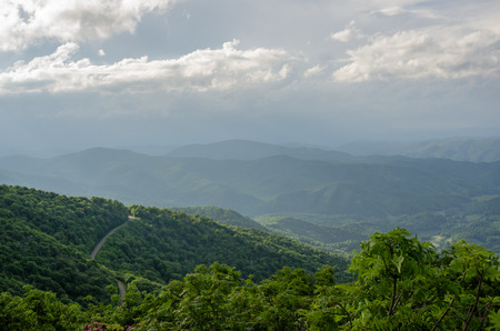 A winding road hugs the side of a mountain as it climbs up towards Roan Mountain Stock Photo