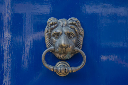 A brass lion knocker stands out against a royal blue door photo