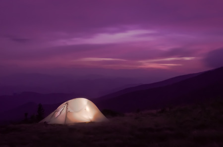 Long exposure of a lit tent standing out against the purple sky as dusk settles in on a high mountain range photo