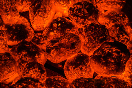 A wide view of hot coals underneath a grill