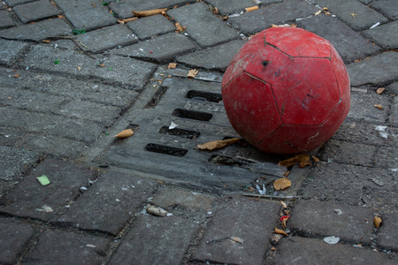 settles: A worn red soccer ball settles in the grate of a gutter