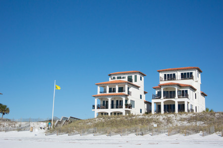 Houses near a public beach access where a yellow flag displays a sign of caution to beach goers photo