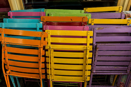 A restaurant stacks colorful chairs to set up for outdoor seating on a sunny day in the Netherlands photo
