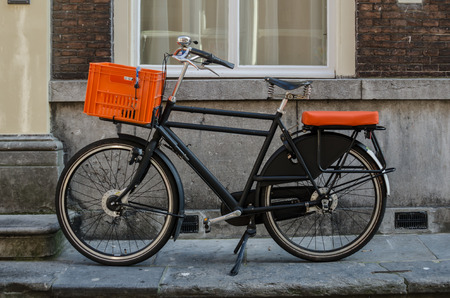 A vintage bicycle with orange accents is parked on a street sidewalk in the Netherlands photo