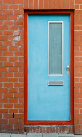 terra cotta: A light blue door contrasts against an orange frame and terra cotta brick Stock Photo