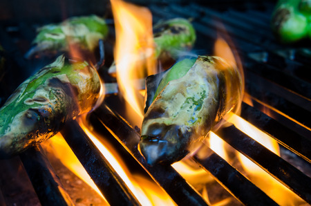 grill: Small green peppers roast on flames on a grill