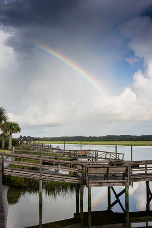waterway: A rainbow arches over thick clouds after a storm. It reflects in the quiet waters of the intercoastal waterway Stock Photo