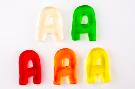 A set of five gummy letters in the shape of A on a white background photo