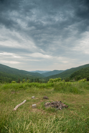 appalachian trail: A fire ring at a campsite along the Appalachian Trail overlooks a vast green valley Stock Photo