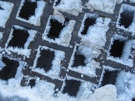 metal grate: Snow and ice clump in the square holes of a metal grate