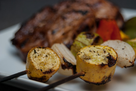 charred: Charred vegetable kabobs with grilled pork in background Stock Photo