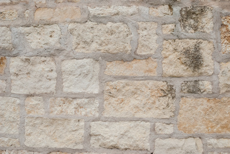 grout: Beige and cream stones in an outdoor wall with thick grout