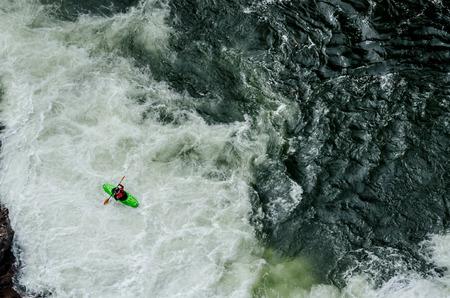 kayaker: A green kayaker paddles through rushing white water Stock Photo