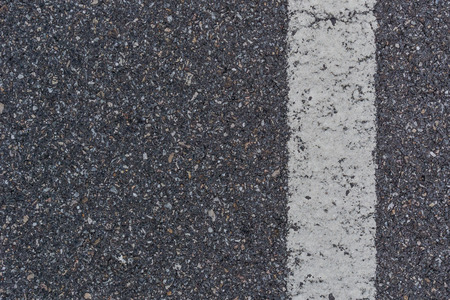 Close up of a white stripe painted on clean blacktop surface