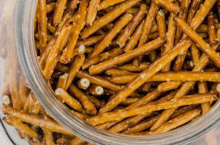 pretzel: A glass jar holds salted pretzel sticks Stock Photo