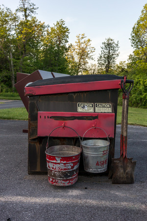 the ashes: A dumpster with buckets with disposing of campfire ashes