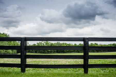 pasture fence: Black painted fence along a horse pasture right before a summer storm Stock Photo