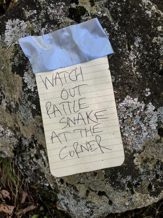 hand written: A handwritten note warns hikers of a rattlesnake around the corner