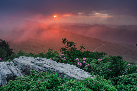jane: A thin layer of fog reflects the pink and orange colors of sunset over Jane Bald Stock Photo