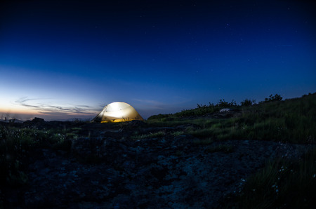 As dusk settles over a mountain range, a tent is lit against a starry sky with lights from the valley below still glowing Stock Photo