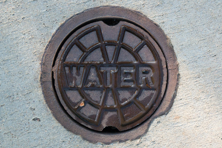 access point: An access point for a  shut off valve to a water main along a sidewalk