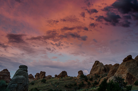 devils garden: The sky lights up in shades of pink with sunrise over rock formations along the Devils Garden Trail