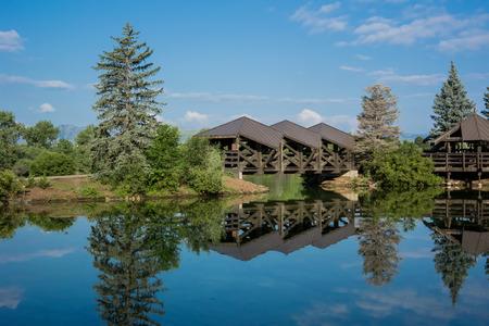 denver city park: A covered bridge over a calm pond in a public park in Denver, Colorado