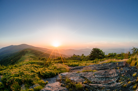 Sun rays fan out as the sun crests the ridge behind Roan Mountain Stock Photo