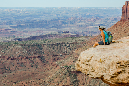 overlook: A female hiker rests on a rock overlooking a vast canyon Stock Photo