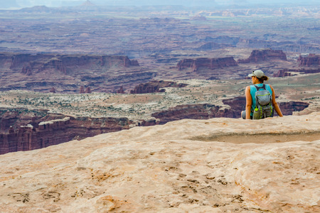A female hiker looks out over a vast canyon on a hike in Utah
