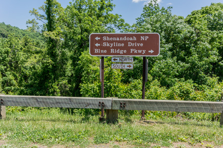 guard rail: A sign near the boundary of Skyline Drive and the Blue Ridge parkway points motorists in the right direction