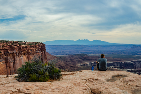 geological feature: A male hiker pauses on a hike to take in a view of the large canyon containing the infamous White Rim road
