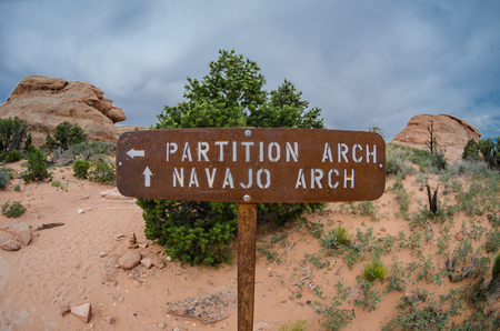 partition: A fisheye view of the sign pointing visitors to Partition and Navajo Arches Stock Photo