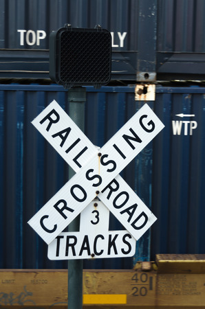 transported: A navy container being transported with a railroad crossing sign in the foreground Stock Photo